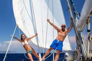 Happy couple having fun on sailboat, young family in water cruis