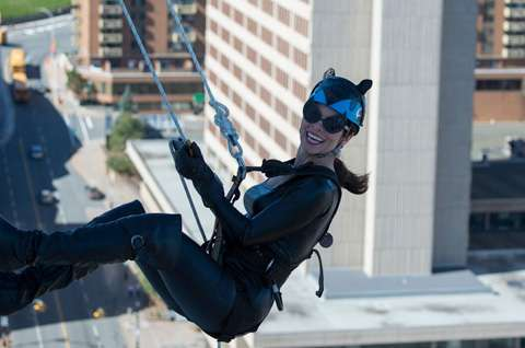 Cat Woman rappelling down a building
