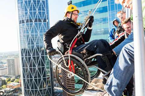 A man in a wheelchair rappelling down a building