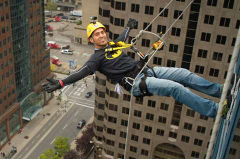 Man rappelling down a building