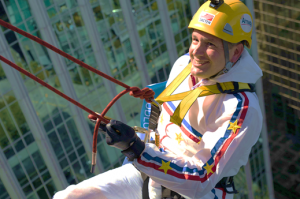 Image of a man dressed in a white jumpsuit with blue and red accent lines on the arm and across shoulder. He is smiling, wearing a yellow helmet and rappelling off a building.
