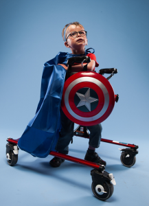 Boy with mobility device dressed in superhero costume