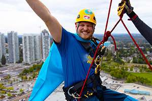 Image of a man, grinning in excitement, wearing a blue caped costume and yellow helmet with his hands punched in the air above him, and holding on a to a rope at the side of the top of a building