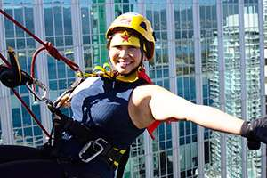 Photo of a smiling woman, wearing a helmet, with her arms stretched to her sides, while hanging off a rope at the side of the top of a building