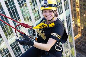 Image of a smiling woman, wearing a yellow helmet and Batman t-shirt, holding on to a rope midway down the side of a building
