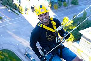 Photo of a smiling man, dressed in black and yellow helmet, harnessed and holding on to a rope, while midway down the side of a building